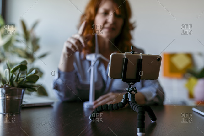 Woman making vlog on mobile phone while sitting at home
