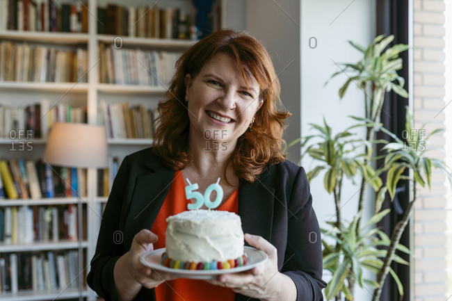 Woman holding cake with number 50 candle while standing at home