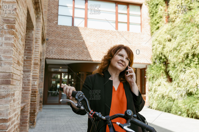 Woman talking on mobile phone while standing by bicycle at front yard