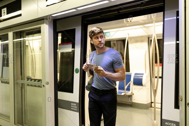 Handsome young male commuter looking away while disembarking from subway train at station