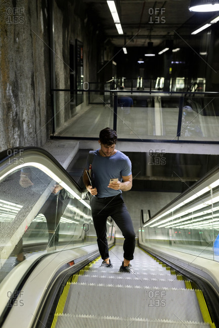 Male commuter using mobile phone while standing on escalator moving up at subway