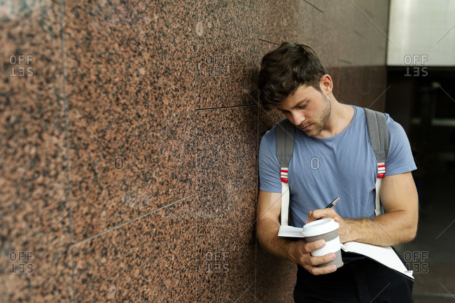 Handsome young man writing in book while holding coffee cup and leaning on brown tile wall at subway station