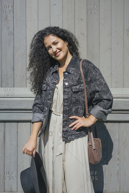 Smiling woman with hand on hip standing against wall
