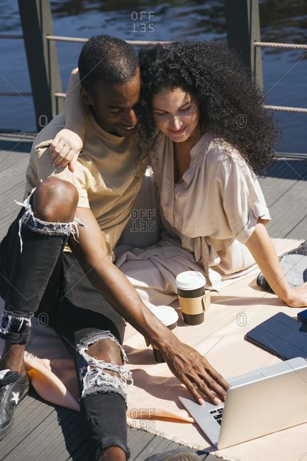 Couple using laptop while sitting on bridge in city