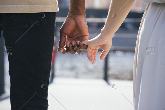 Couple holding finger while standing on footpath in city