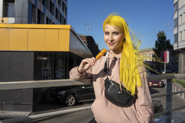 Dyed yellow hair woman eating ice cream while standing on bridge during sunny day