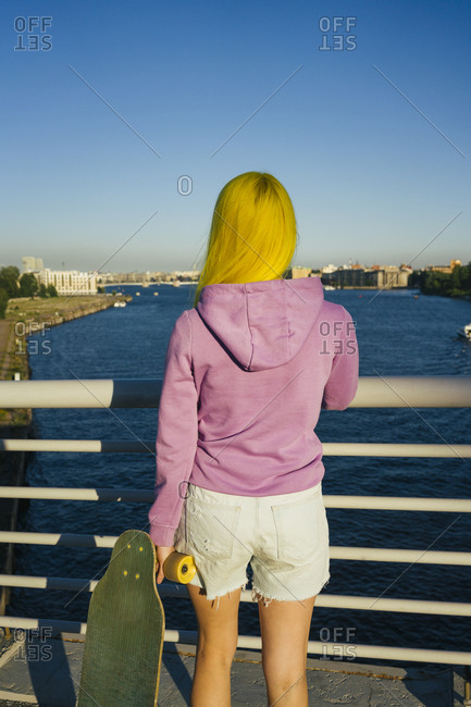 Young woman looking at sea while standing on bridge during sunny day