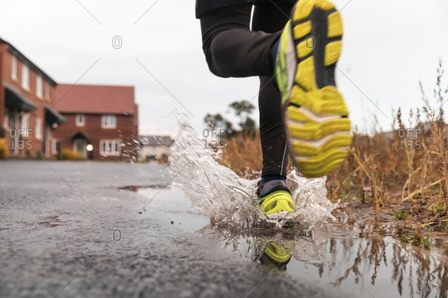 Low section of man running in water puddle during rainy season