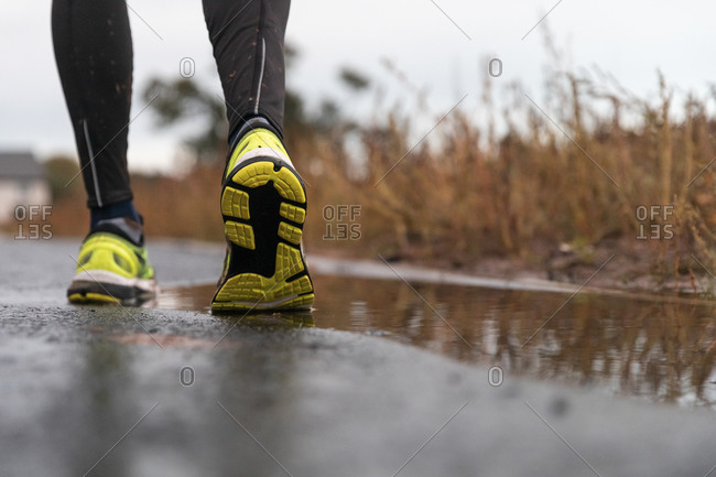 Low section of man walking on road during rainy season