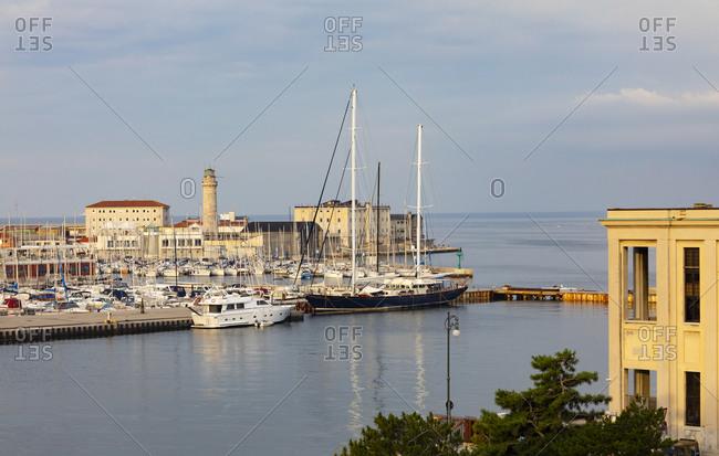 Italy- Friuli Venezia Giulia- Trieste- Boats moored in San Giusto Sea Center marina withLa Lanterna lighthouse in background