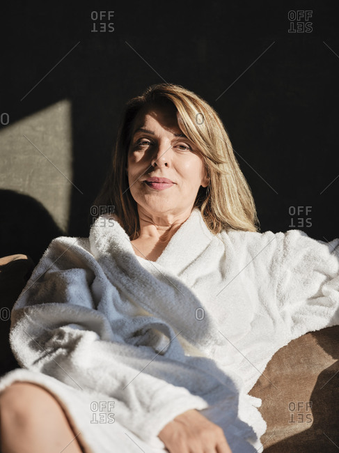 Beautiful elderly woman relaxing while sitting on sofa in hotel