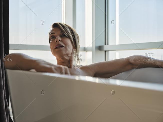 Blond senior woman taking bath in bathtub against window at luxury hotel room
