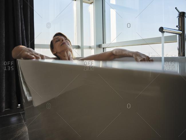 Relaxed senior woman taking bath in bathtub against window at luxury hotel room