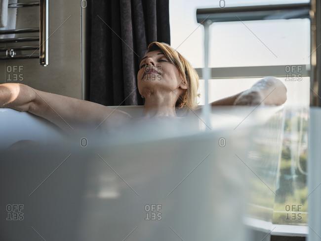 Relaxed blond senior woman taking bath in bathtub against window at luxury hotel room
