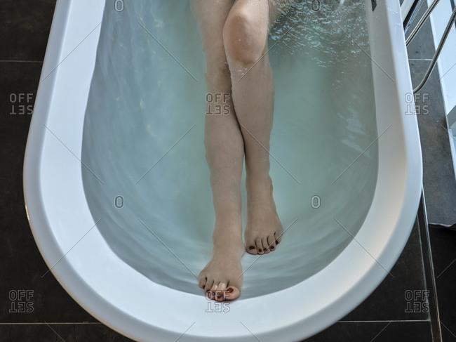 Senior woman taking bath in bathtub at luxury hotel room