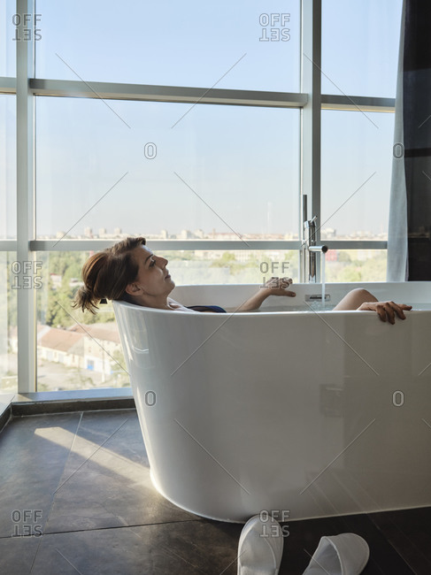 Relaxed retired elderly woman on vacation taking bath in bathtub against window at luxury hotel room