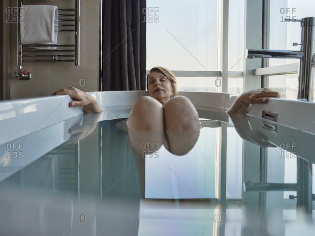 Retired woman taking bath in bathtub against window at luxury hotel room