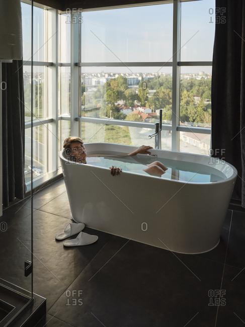 Woman taking bath in bathtub against window at luxury hotel room