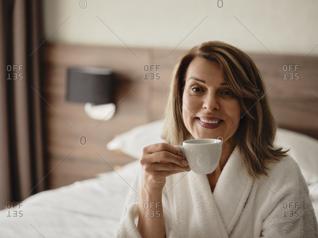 Smiling beautiful blond woman drinking coffee while sitting on bed at hotel room