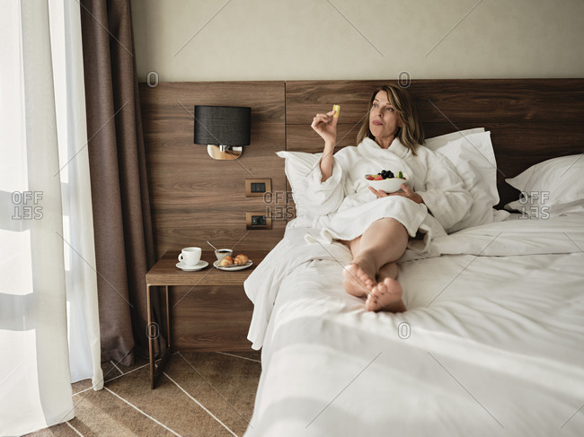 Senior woman eating fresh fruits in breakfast while relaxing on bed and looking away at hotel room