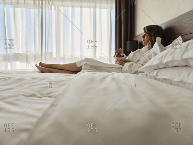 Senior woman eating fresh fruits while relaxing on bed at hotel room