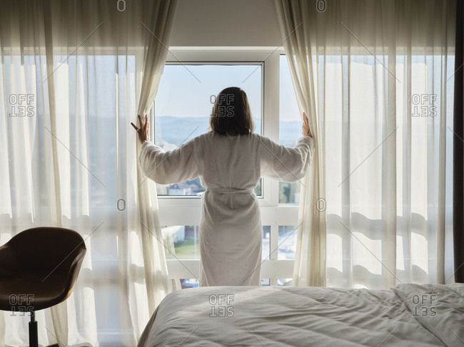 Woman opening white curtain while looking through window at luxury hotel room