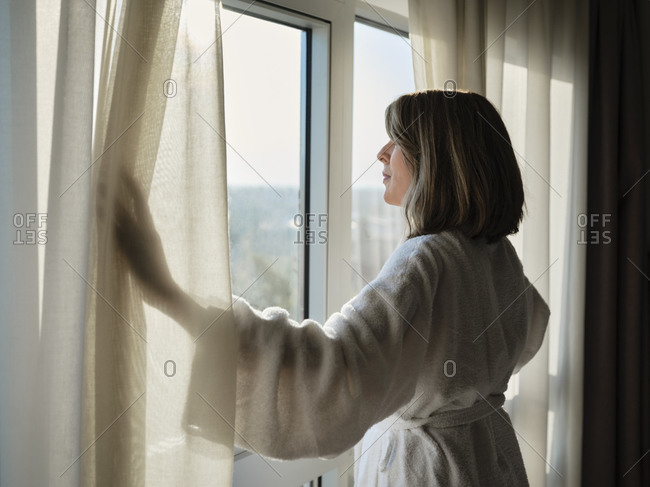 Blond senior woman opening white curtain while looking through window at luxury hotel room
