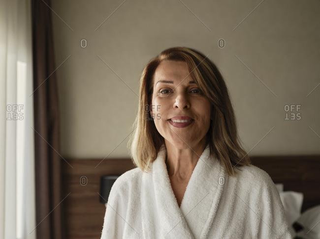 Happy blond elderly woman in luxury hotel room