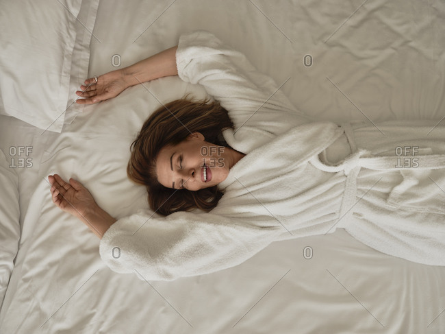 Smiling senior woman lying on white bed at luxury hotel room