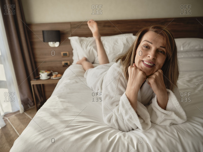 Happy beautiful elderly woman lying on bed at hotel room