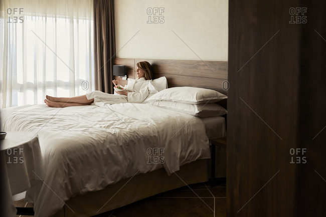 Retired woman eating fresh fruits while relaxing on bed at hotel room during vacation