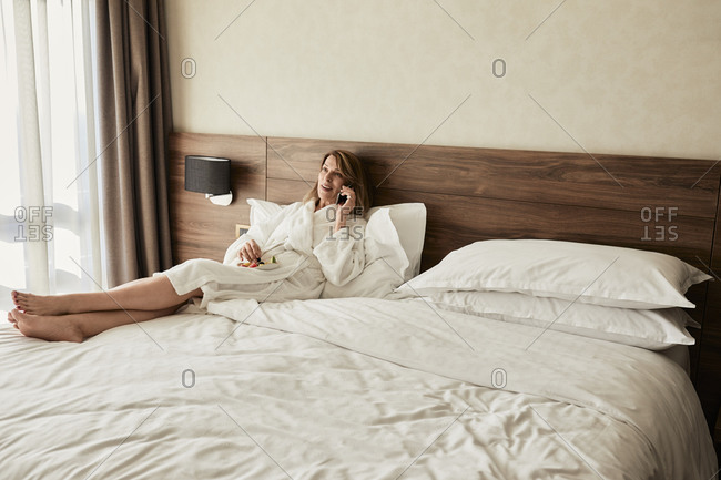 Senior woman talking through mobile phone while reclining on bed with fruit in hotel room