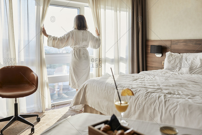 Retired senior woman opening curtain while looking through window at luxury hotel room