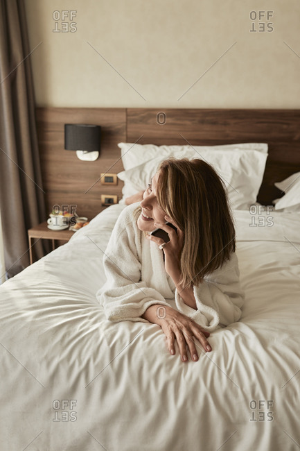 Smiling elderly woman talking on phone while looking away and lying on bed in hotel room