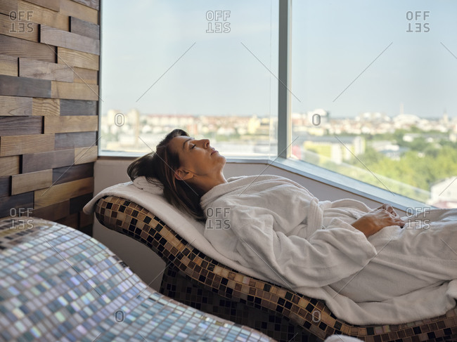 Senior woman lying down on lounge chair at health spa