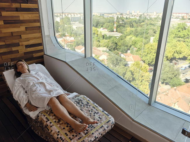 High angle view of senior woman relaxing while lying on lounge chair at health spa