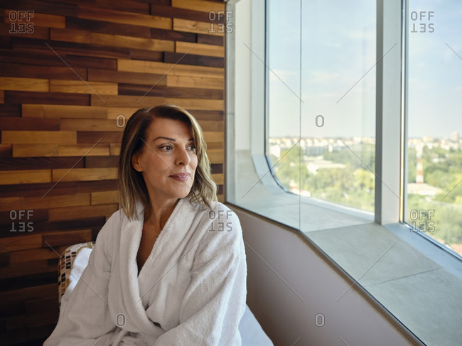 Blond senior woman looking through window while sitting on lounge chair