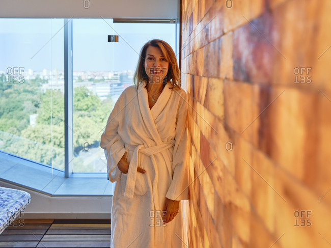 Senior woman standing by wall at health spa
