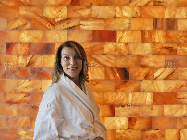 Senior woman standing against wall at health spa