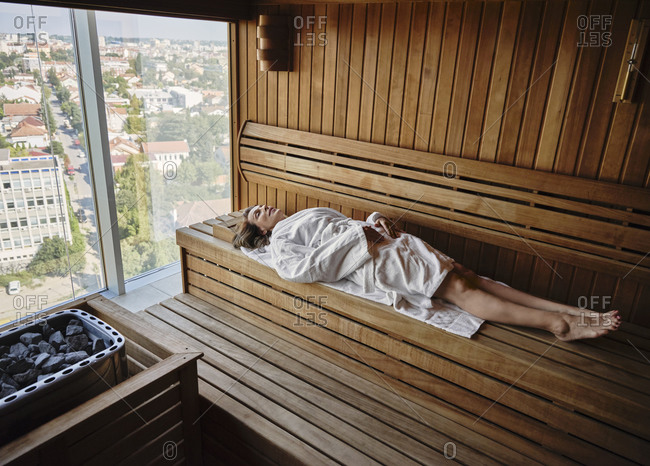 Senior woman relaxing in wooden sauna while lying down at health spa