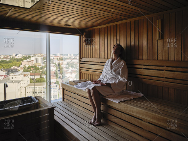 Relaxing senior woman sitting on wooden sauna at health spa