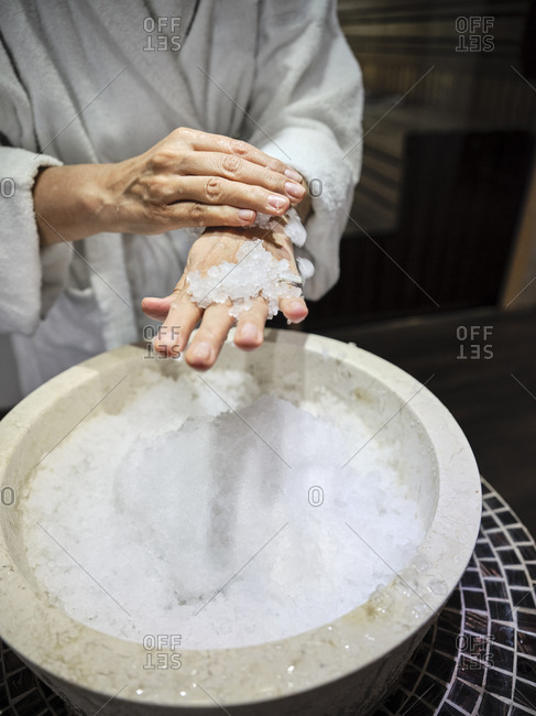 Midsection of senior woman rubbing ice on hands at spa