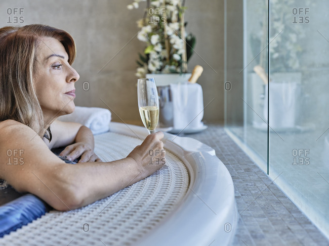 Senior woman looking through window while holding wine in swimming pool