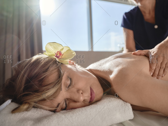 Mature female giving back massage to senior woman in spa