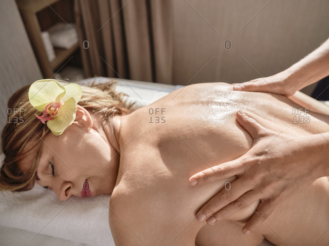 Hand of mature woman giving back massage to senior woman