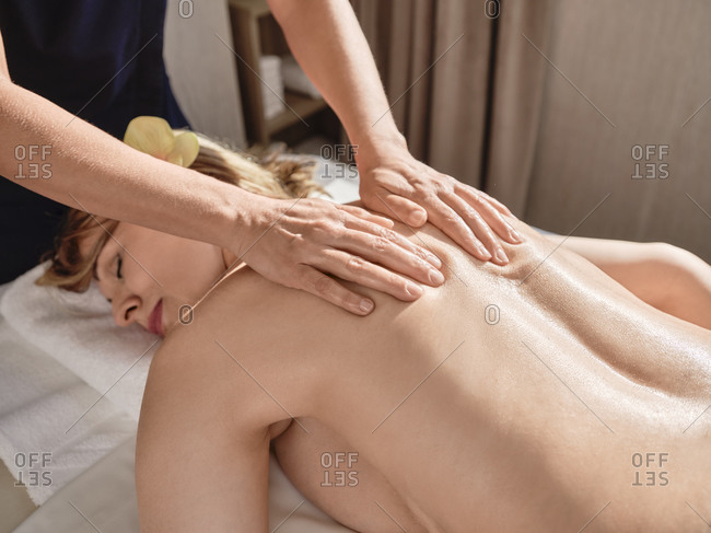 Mature woman giving back massage to senior female at health spa