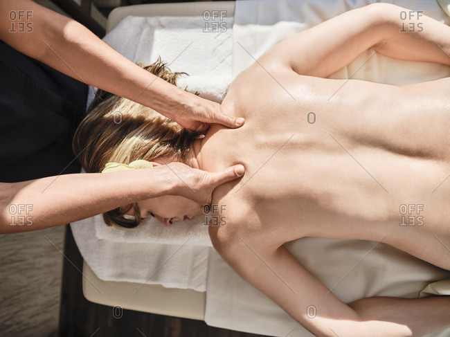 Hands of mature female giving massage to senior woman at spa