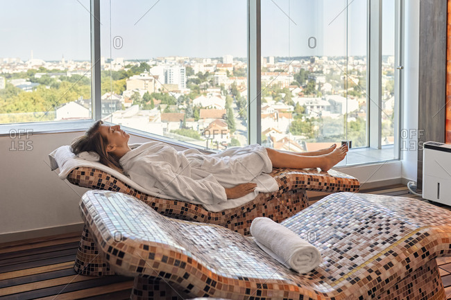 Senior female reclining on lounge chair at health spa
