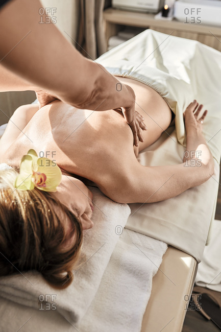 Hand of mature female giving massage to senior woman at health spa