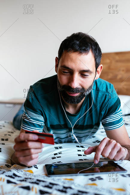 Man shopping online on a tablet lying on the bed at home